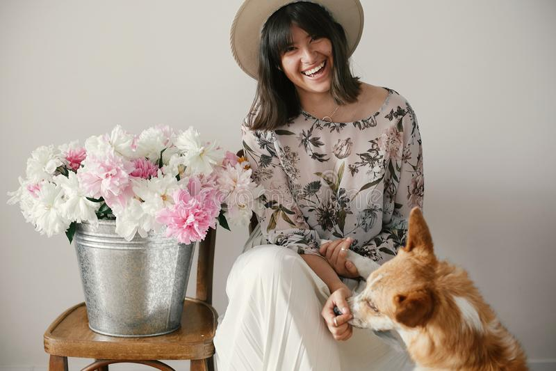 Stylish boho girl sitting at metal bucket with peonies on rustic wooden chair and playing with cute golden dog.Beautiful hipster stock images