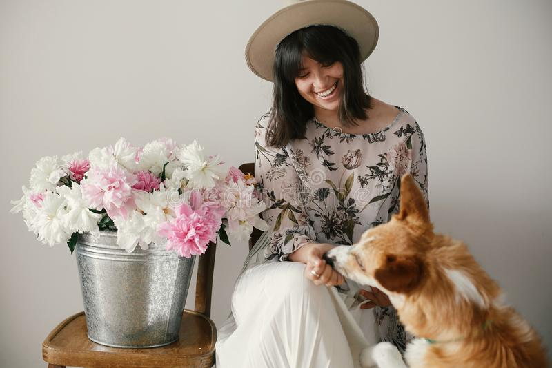 Stylish boho girl sitting at metal bucket with peonies on rustic wooden chair and playing with cute golden dog.Beautiful hipster royalty free stock photo