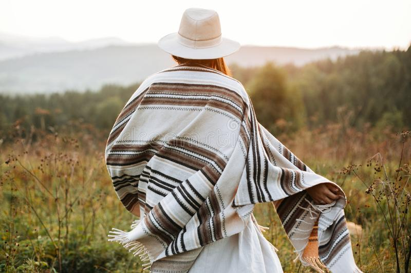 Stylish boho girl walking in sunny light at atmospheric sunset in meadow. Happy hipster woman in poncho and hat enjoying traveling stock image