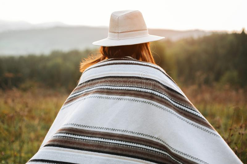 Stylish boho girl walking in sunny light at atmospheric sunset in meadow. Happy hipster woman in poncho and hat enjoying traveling stock photography