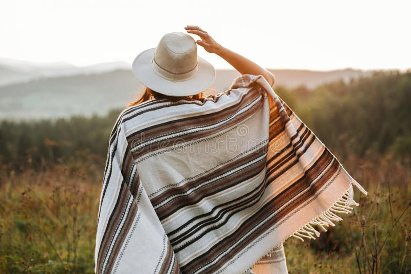 Stylish boho girl walking in sunny light at atmospheric sunset in meadow. Happy hipster woman in poncho and hat enjoying traveling royalty free stock image