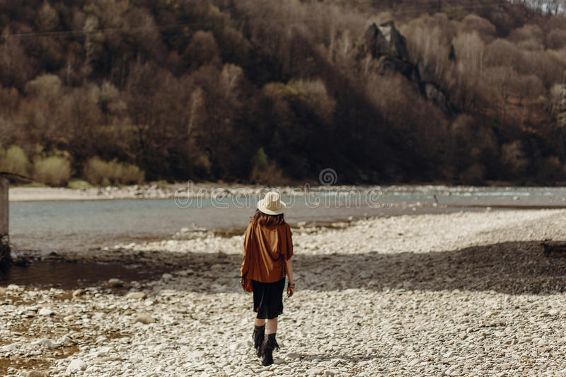stylish boho traveler woman in hat back view, fringe poncho posing near water river beach in mountains, gypsy hipster girl. royalty free stock images