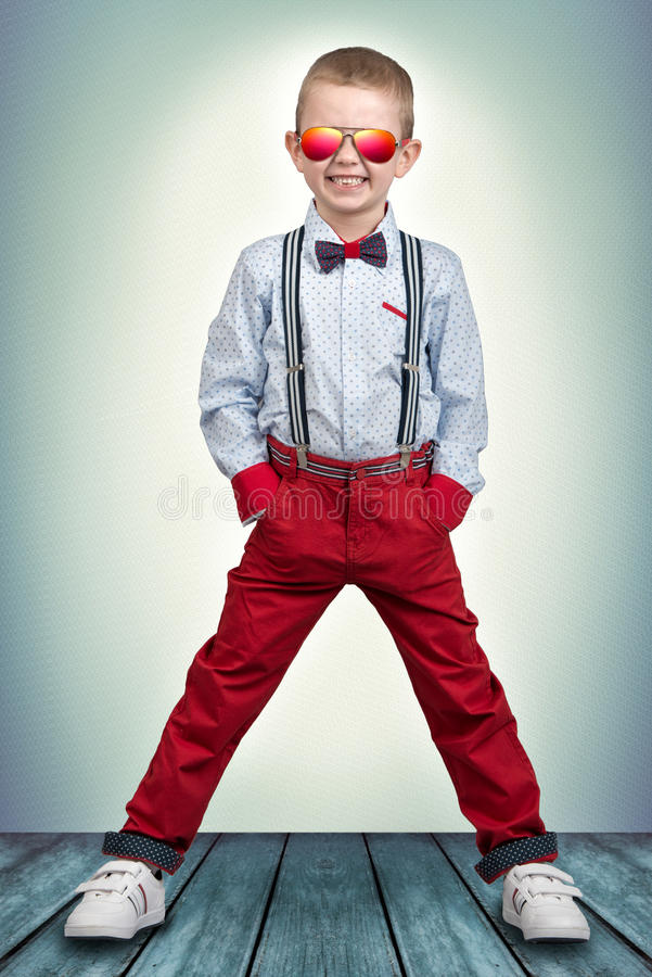 Stylish boy in fashionable clothes and sunglasses from the sun . Children`s fashion. Boy in fashionable clothes and sunglasses from the sun royalty free stock photography