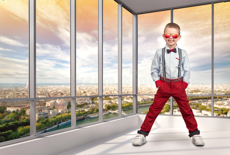 Stylish boy in fashionable clothes and sunglasses from the sun in the office. Children`s fashion. Boy in fashionable clothes and sunglasses from the sun in the stock images