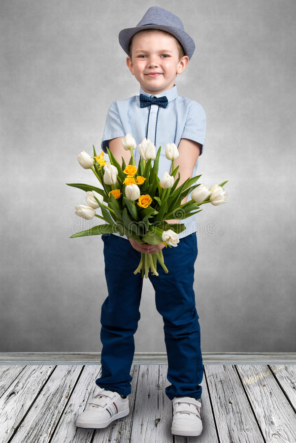 Stylish boy in a hat holding a bouquet of spring tulips.Children`s fashion. Stylish boy in a hat holding a bouquet of spring tulips royalty free stock photos