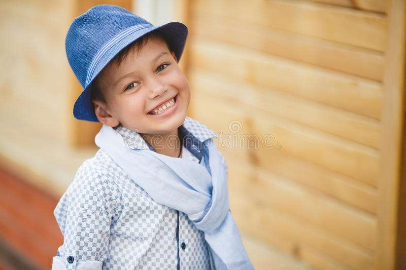 Stylish boy in the street near his home. Stylish boy,brunette with short hair, on his head wearing a fashionable hat in dark grey,wearing a plaid light shirt ,on stock images