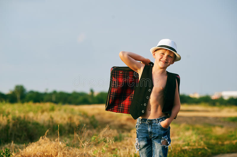 Stylish boy with suitcase on rural road royalty free stock images
