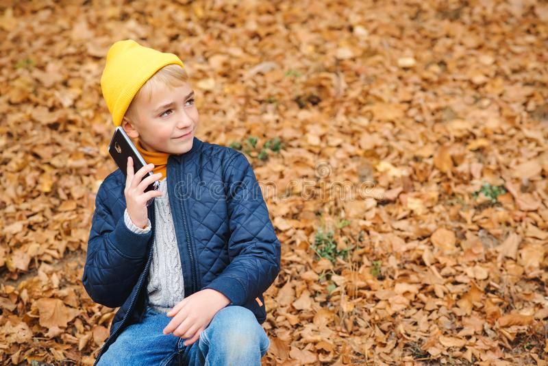 Stylish boy talking on cell phone outdoors. Kid on a walk in autumn park. People, technology and communication concept. Little boy stock photo