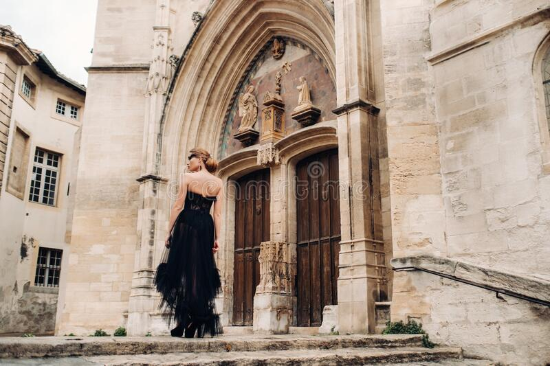 A stylish bride in a black wedding dress poses in the ancient French city of Avignon. Model in a beautiful black dress. Photo. Shoot in Provence stock photography