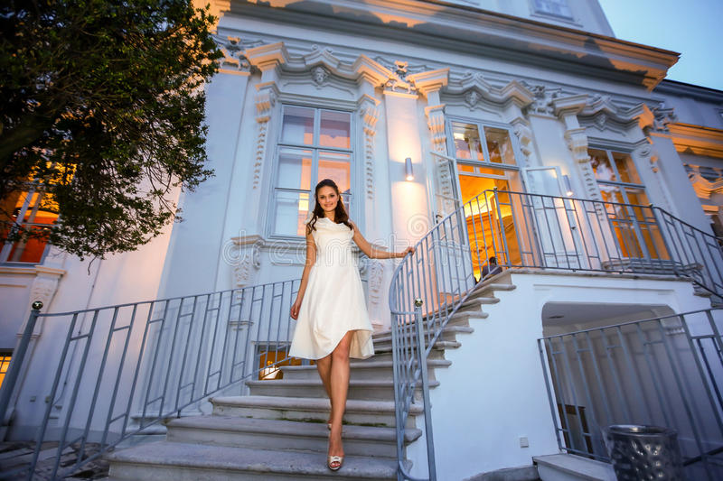 Stylish bride goes on stairs evening background castle Vienne A. Ustria stock images