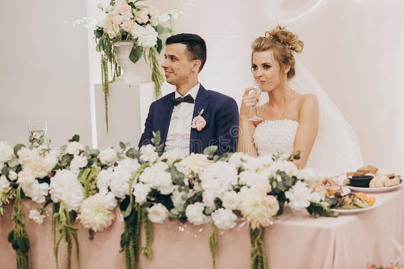 Stylish bride and groom sitting together at beautiful pink centerpiece decorated with flowers at wedding reception in restaurant. royalty free stock image