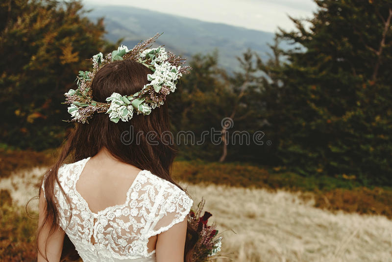 stylish bride posing with bouquet on background of forest, luxury boho wedding at mountains royalty free stock photo