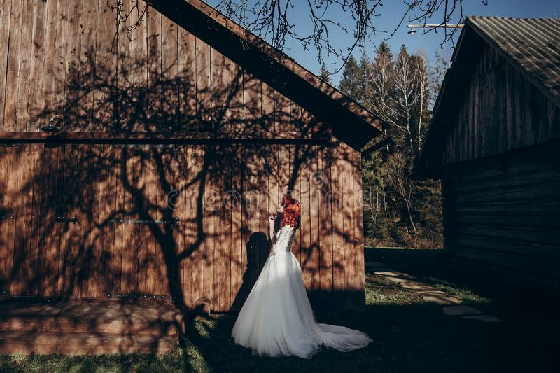 Stylish bride relaxing in sunlight on background of wooden wall in country. rustic wedding concept in barn, space for text. happy royalty free stock image