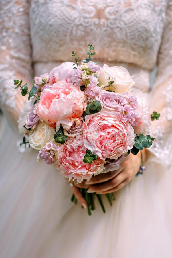 Stylish bride in a white dress holds an unusual wedding bouquet close-up. Delicate wedding bouquet of different flowers royalty free stock photo