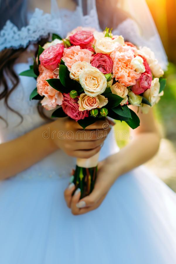 Stylish bride in a white dress holds an unusual wedding bouquet close-up. Delicate wedding bouquet of different flowers. In the hands of the bride, selective royalty free stock photo