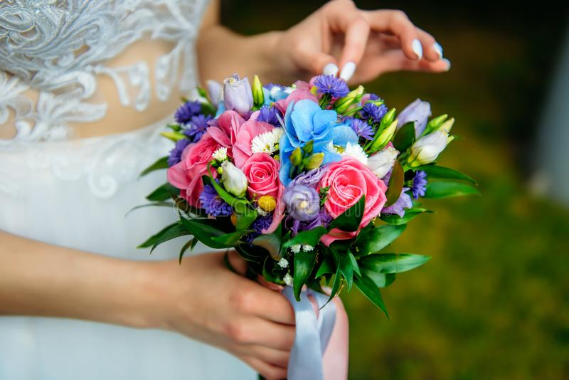 Stylish bride in a white dress holds an unusual wedding bouquet close-up. Delicate wedding bouquet of different flowers. In the hands of the bride, selective stock photography