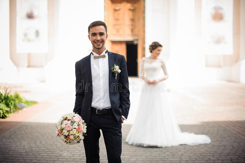 Bridegroomis holding a wedding bouquet and smiling royalty free stock photography