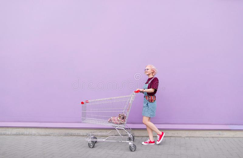 Fashionable young girl with shopping carts walking down the street on the background of a purple wall stock photos