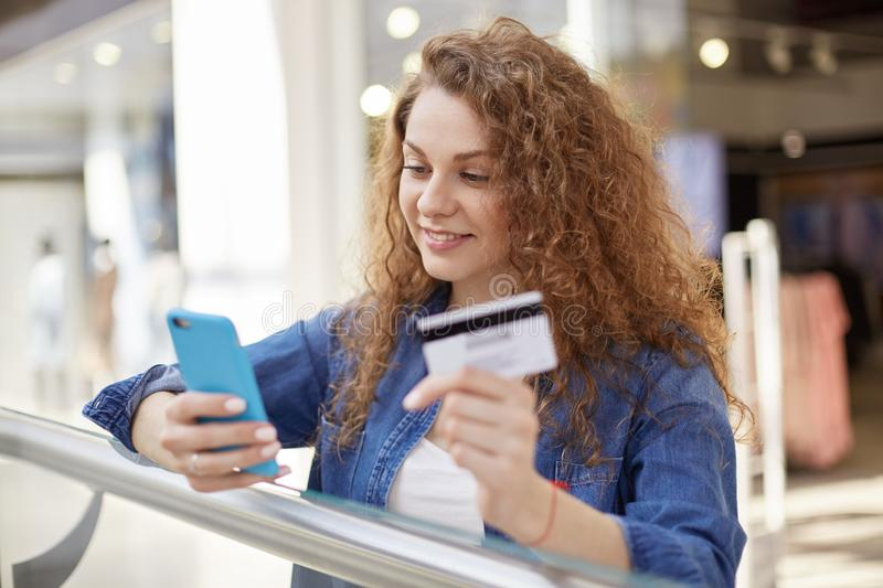 Stylish and bright woman reads notice that lot of money was received on account. Agitated mistress checks information on internet. She holds credit card in royalty free stock photo
