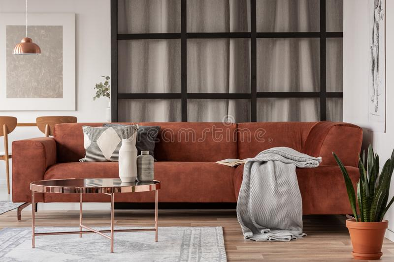 Stylish brown corner sofa with patterned pillows in elegant living room interior with mullions wall stock photography