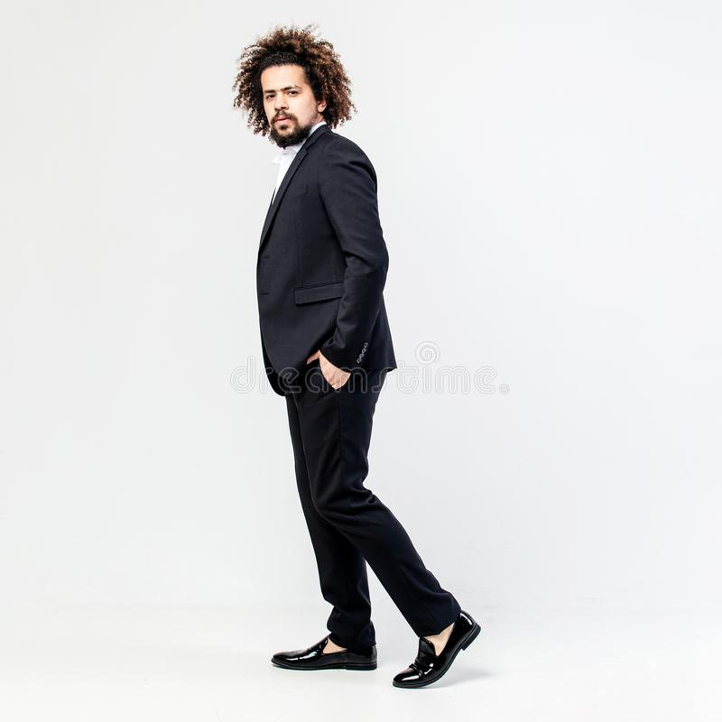 Stylish brown-haired curly guy dressed in a classic black suit and white shirt poses in the studio on the white royalty free stock images