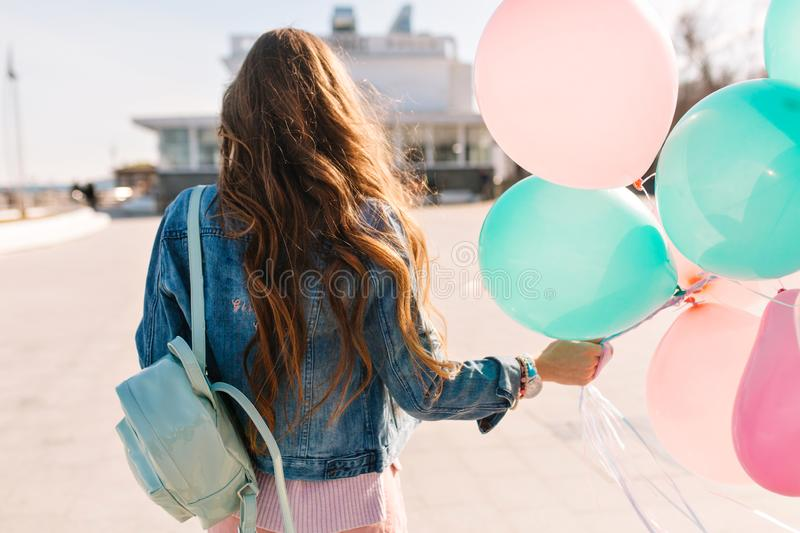 Stylish brunette girl with colofrul balloons walking down the street enjoys sunny day. Young curly woman wearing denim. Jacket with trendy backpack going to royalty free stock photo