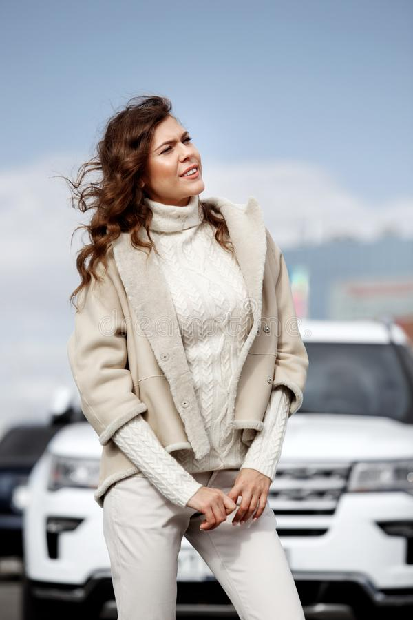 Stylish brunette girl dressed in stylish knitted white sweater, light pants and a short sheepskin coat poses against of royalty free stock photos