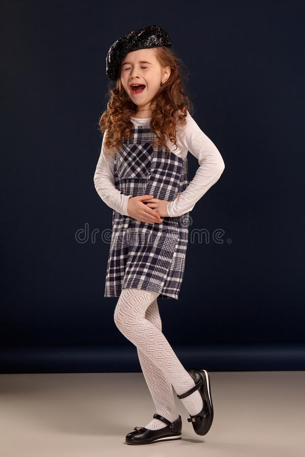 Stylish brunette kid is posing in studio on a black background. Children`s fashion. royalty free stock photos