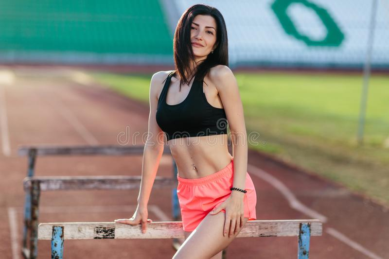 Stylish brunette woman in pink shorts and tank top posing for the camera on running track near the barriers running jumping at the. Stadium royalty free stock images