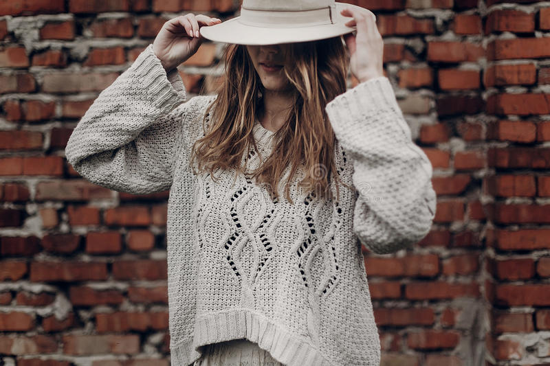 Stylish brunette woman in white hat and boho white sweater posing near red brick wall royalty free stock images