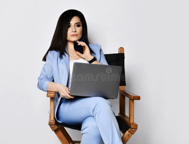 Business woman in blue official suit sits with laptop on armchair and holds her cell phone at her chin pondering talk royalty free stock photo