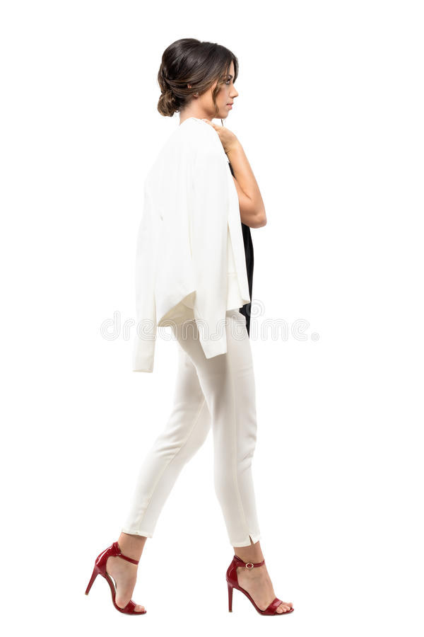 Stylish business woman in white suit walking and carrying jacket over shoulder. Side view. royalty free stock photography