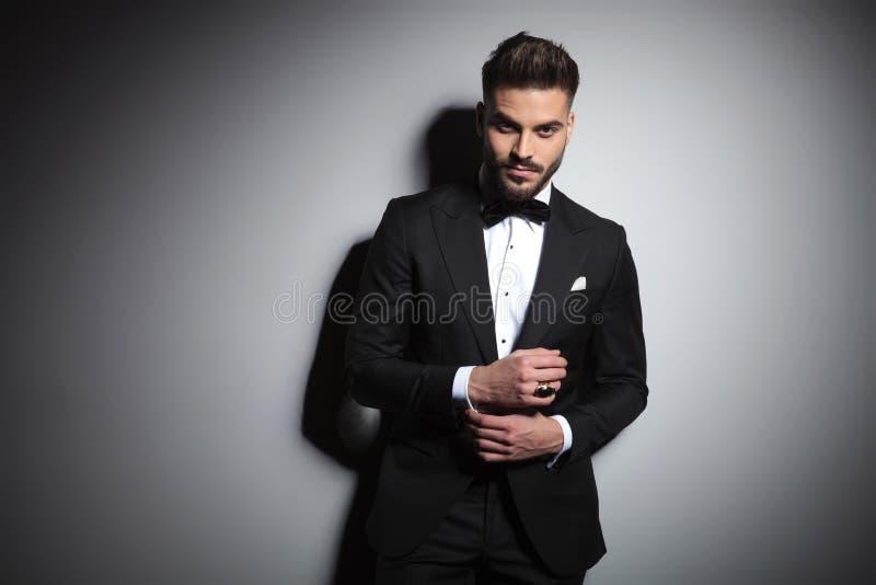 Stylish businessman in black tuxedo adjusting his sleeve. On grey studio background royalty free stock photos