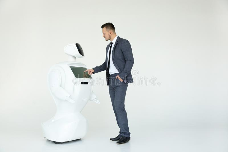 A stylish businessman communicates with a robot. Cybernetic system today. Modern Robotic Technologies. Humanoid. A robot with human face and body - humanoid royalty free stock image