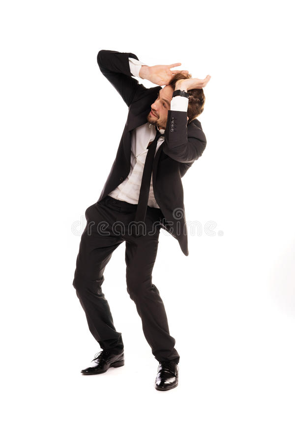 Stylish businessman cowering in fear. With his hands raised to protect his head leaning backwards, isolated on white stock photos