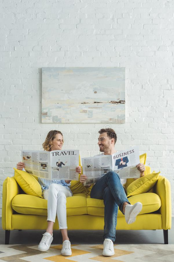Stylish businessman with girlfriend reading newspapers about business. And travel stock photos