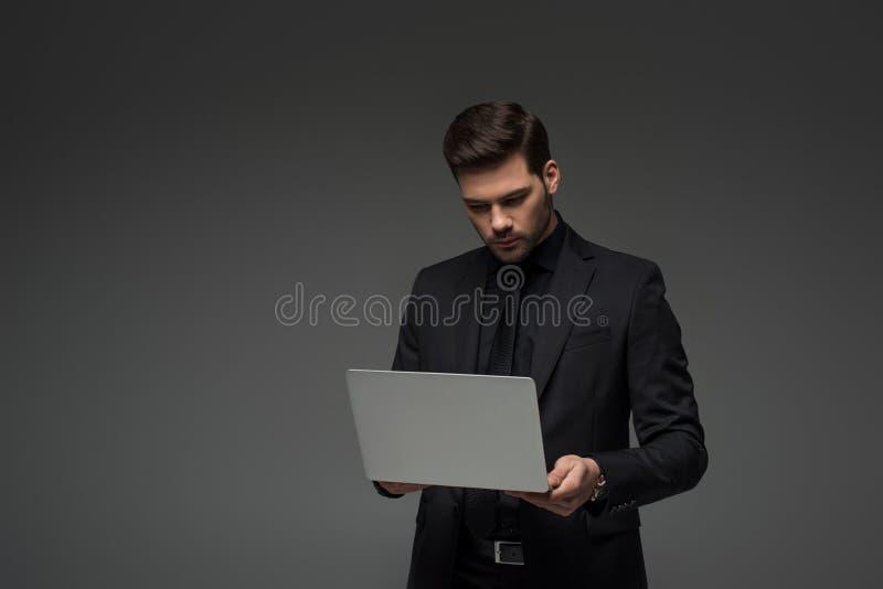 Stylish businessman holding laptop isolated. On grey stock photo