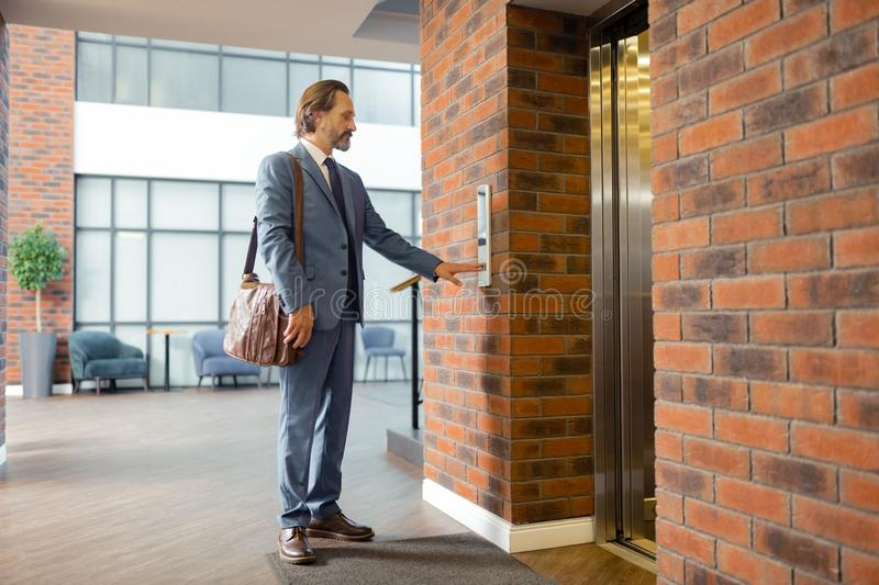 Stylish businessman leaving business center in the evening. Leaving business center. Stylish mature bearded businessman leaving business center in the evening stock photo