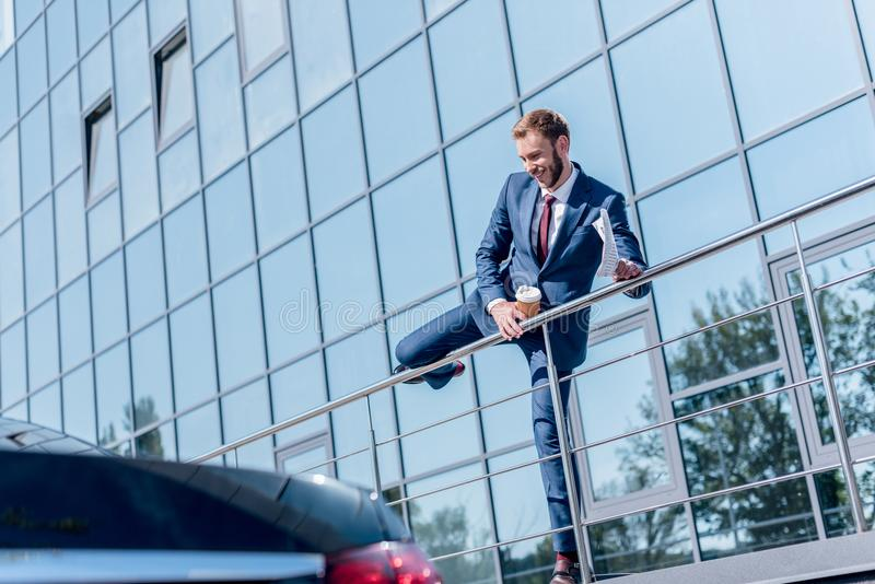 Stylish businessman with newspaper and disposable cup of coffee standing. At office building stock images