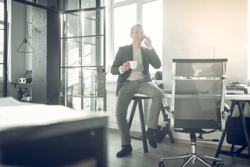 Stylish businessman sitting on table and calling his business partner. Sitting on table. Stylish businessman sitting on table and calling his business partner royalty free stock image