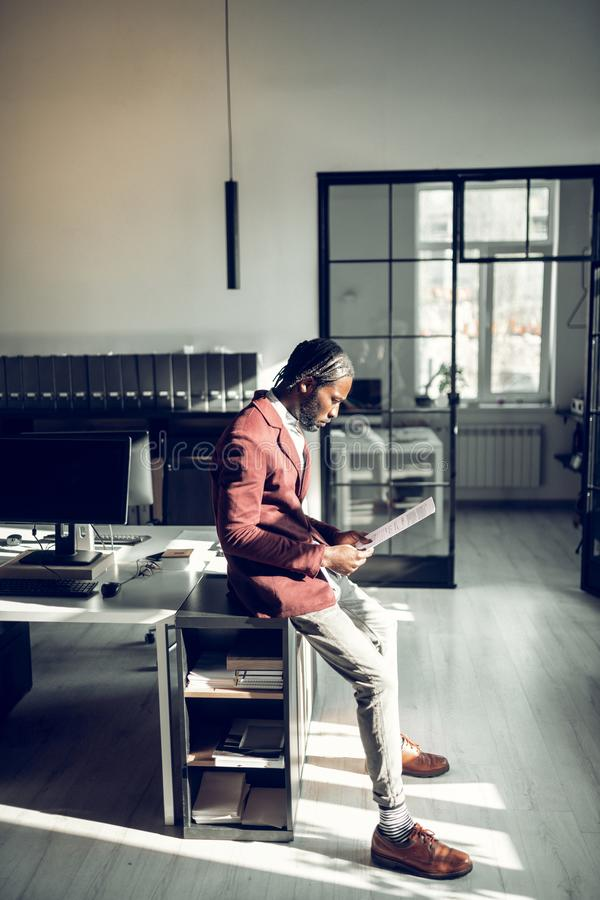 Stylish businessman standing near working table and reading. Near working table. Stylish dark-skinned businessman standing near working table and reading stock images