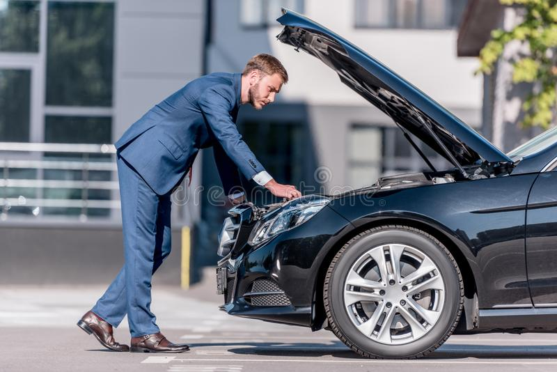 stylish businessman in suit repairing car royalty free stock images