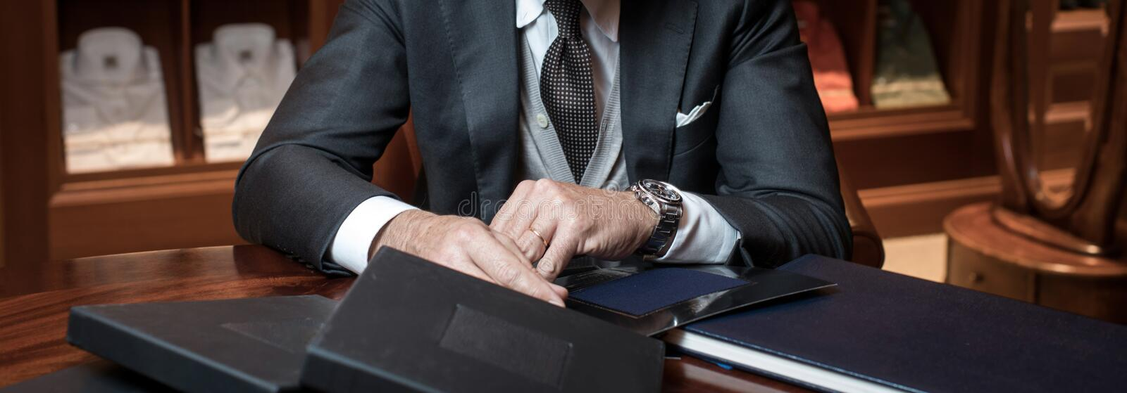Stylish businessman at table. Unrecognizable stylish businessman in suit sitting at table in wardrobe stock photography
