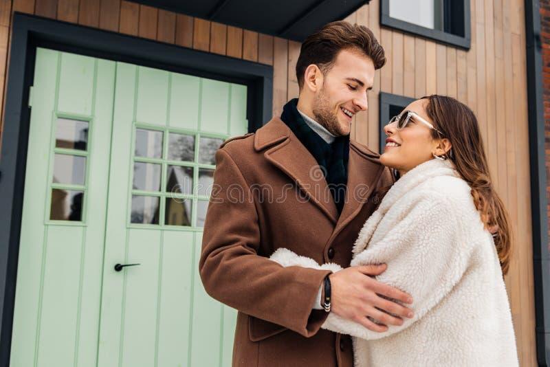 Stylish businessman wearing brown coat hugging his future wife stock photos