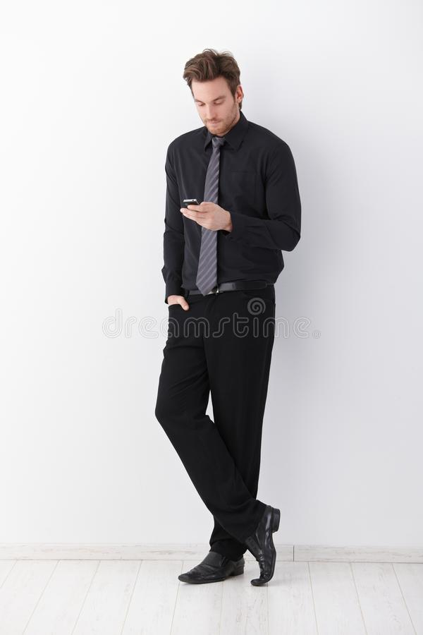 Stylish businessman writing text message. Stylish businessman standing over white background, writing text message stock photos