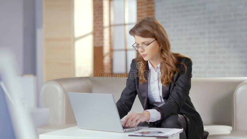 Stylish businesswoman or lawyer working on laptop at company office, technology royalty free stock photos