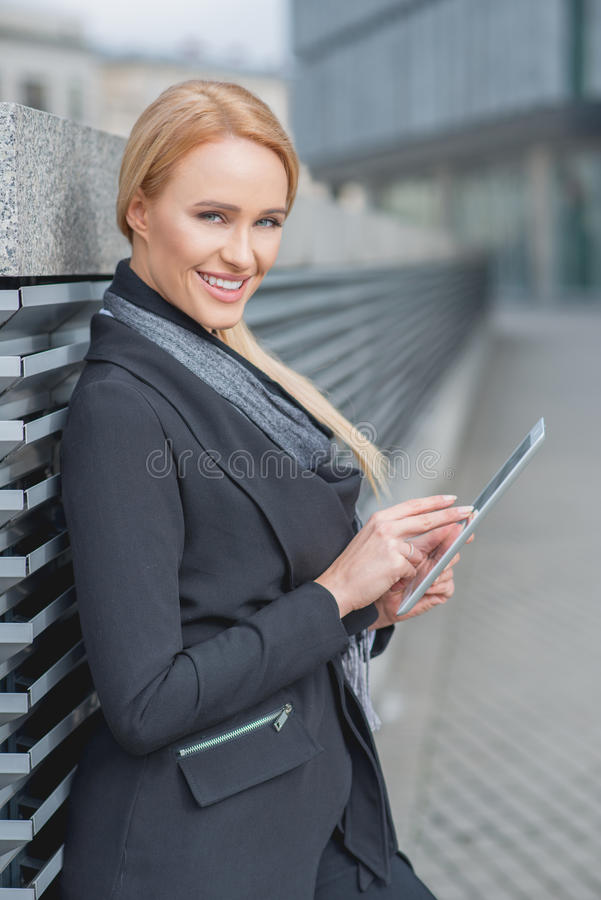 Stylish businesswoman using a tablet-pc. As she leans against a metal louver along an urban walkway smiling at the camera royalty free stock photo
