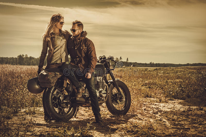 Stylish cafe racer couple on the vintage custom motorcycles in a field. Young, stylish cafe racer couple on the vintage custom motorcycles in a field royalty free stock image