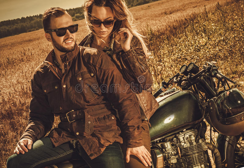 Stylish cafe racer couple on the vintage custom motorcycles in a field. Young, stylish cafe racer couple on the vintage custom motorcycles in a field royalty free stock photo