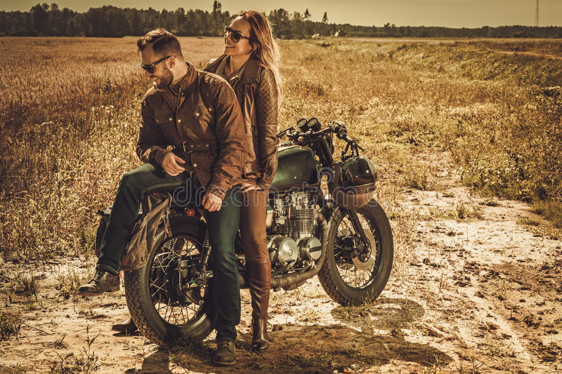 Stylish cafe racer couple on the vintage custom motorcycles in a field. Young, stylish cafe racer couple on the vintage custom motorcycles in a field stock photo